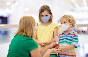 woman sanitizing children's hand